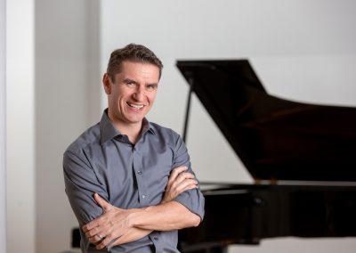Pianist Ernst posiert vor dem Klavier
