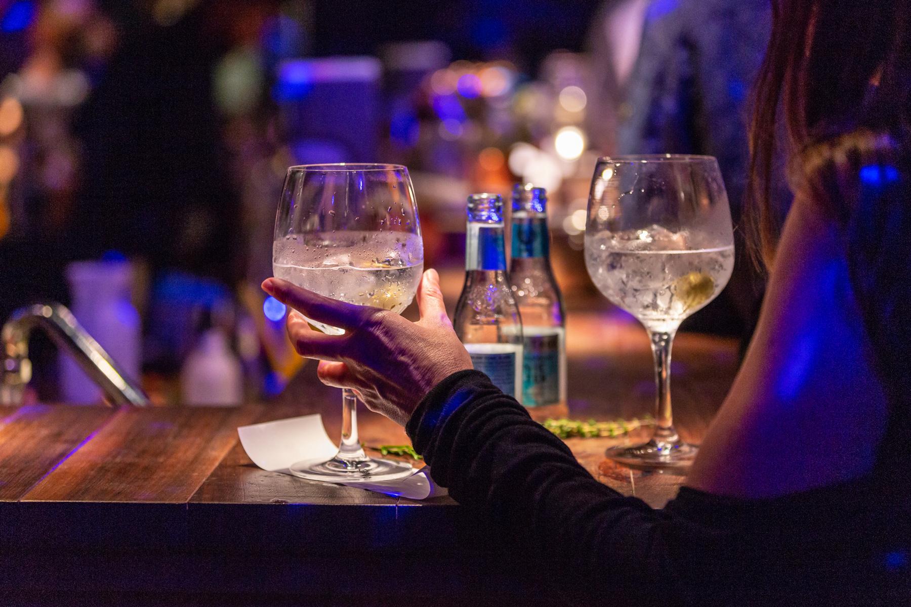 Frau greift nach einem Glas Cocktail